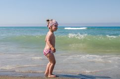 Little charming baby girl standing happy on a sandy beach on the shore of the Tyrrhenian Sea, on a clear summer sunny day Stock Photos