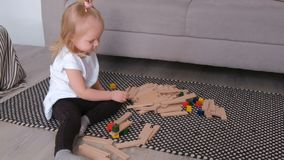 Little charming blond girl building wood blocks sitting near the sofa. Experiments with blocks.