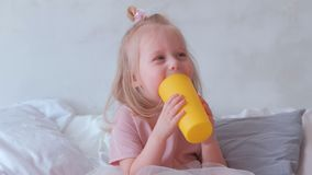 Little charming blond girl in pink dress plays with yellow plastic cup with her mom. Little charming blond girl in pink dress plays with yellow plastic cup with stock video footage