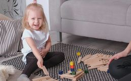 Little charming blond girl playing wood blocks with her mom sitting near the sofa. royalty free stock photo