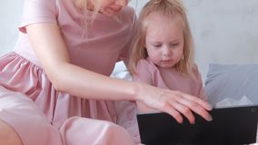 Little charming blond girl selects an application on tablet with her mom. Little charming blond girl selects an application on tablet with her mom stock video