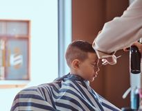 Little charming boy is getting trendy haircut from mature hairdresser at fashionable hairdressing salon.  stock photo
