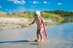 Little charming girl baby playing on the lake swimming in the water during vacation at the resort on a sandy beach Stock Image