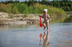 Little charming girl baby playing on the lake swimming in the water during vacation at the resort on a sandy beach Stock Images