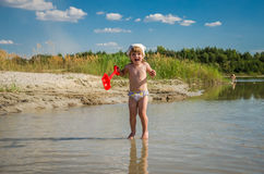 Little charming girl baby playing on the lake swimming in the water during vacation at the resort on a sandy beach Royalty Free Stock Photos