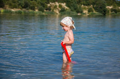Little charming girl baby playing on the lake swimming in the water during vacation at the resort on a sandy beach Royalty Free Stock Photo