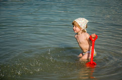 Little charming girl baby playing on the lake swimming in the water during vacation at the resort on a sandy beach Stock Photos