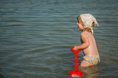 Little charming girl baby playing on the lake swimming in the water during vacation at the resort on a sandy beach Stock Photo