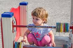 Little charming girl baby playing on the playground riding on a swing, counting the colored shapes Royalty Free Stock Photography