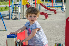 Little charming girl baby playing on the playground riding on a swing, counting the colored shapes Stock Photo