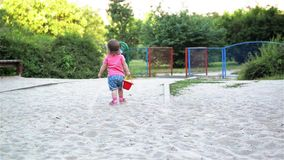 Little charming girl baby playing on the playground in the sandbox, sand mound in the bucket and goes with a bucket in. Hand, children's games stock video