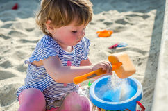 Little charming girl baby playing on the playground in the sandbox sand mound in the bucket with a shovel and rake Royalty Free Stock Photo