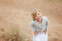 Little charming girl with brown eyes on a background of sand smi Stock Image