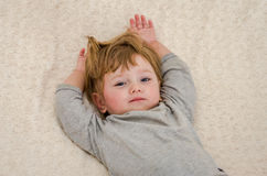 Little charming girl child, baby with pierced ears pierced on the bed in the morning when waking up and stretching raises his hand Royalty Free Stock Images