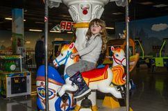 LVIV, UKRAINE - NOVEMBER 2017: Little charming girl the child goes for a ride in an amusement park on the carousel and plays video Stock Photos