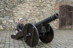 Little charming girl child at the historic ancient cannon in the old castle of the fortress.  royalty free stock photos