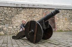 Little charming girl child at the historic ancient cannon in the old castle of the fortress.  royalty free stock images