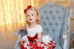 Little charming girl cute blonde with blue eyes in red dress sit Royalty Free Stock Photo