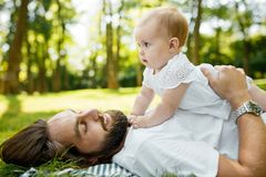 Little charming girl dressed in the white dress is lying on the father`s chest outdoor on a warm sunny day. stock photography