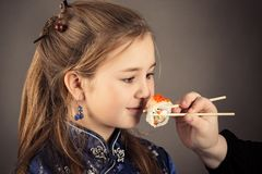 Little charming girl eating roll, humor portrait stock images