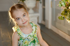 Little charming girl with pigtails in a green dress sitting on the floor, close-up Royalty Free Stock Photography
