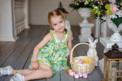 Little charming girl with pigtails in a green dress sitting on t Royalty Free Stock Images