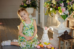 Little charming girl with pigtails in a green dress sitting on t Royalty Free Stock Photos