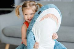 A little charming girl in a red dress is playing. With a big blue toy shark near gray sofa stock image
