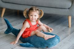 A little charming girl in a red dress is playing. On a gray floor with a big blue toy shark stock image