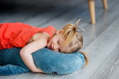 A little charming girl in a red dress is playing. On a gray floor with a big blue toy shark royalty free stock photos
