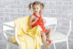 Little charming girl in a red dress is sitting on a white sofa. Next yellow knitted blanket is lying . Behind we see the gray brick wall royalty free stock photos