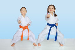 Little cheerful athletes in kimono beat punch hand Royalty Free Stock Photo