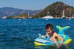 Little cheerful baby floats on the sea in an inflatable boat the shark royalty free stock photos
