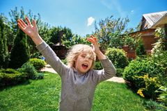 Little cheerful blonde girl is having fun on the lawn near her house royalty free stock image