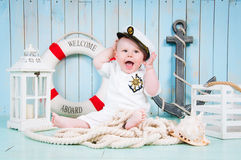 A little cheerful boy captain in the maritime interior Royalty Free Stock Photos