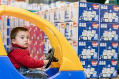a little cheerful boy in red sweater in a children& x27;s car in a shopping center on a background of diapers stock photos