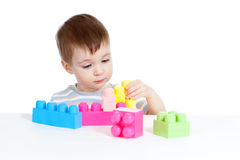 Little cheerful child with construction set stock photos