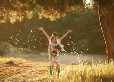 Little cheerful girl and boy in sunny glade. Royalty Free Stock Photos