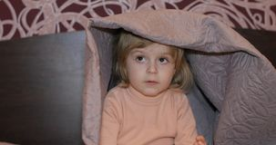 Little cheerful girl hides under blanket and watching TV. Concept of kids sleep stock images