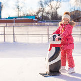 Little cheerful girl learning to skate on the rink Royalty Free Stock Photos