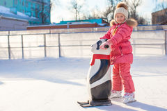 Little cheerful girl learning to skate on the rink Royalty Free Stock Photo