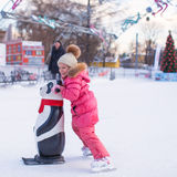 Little cheerful girl learning to skate on the rink Royalty Free Stock Images