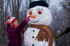 A little cheerful girl look at funny snowman face. A cute little girl has fun in winter park, wintertime Stock Photography
