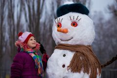 A little cheerful girl look at funny snowman face. A cute little girl has fun in winter park, wintertime Royalty Free Stock Image