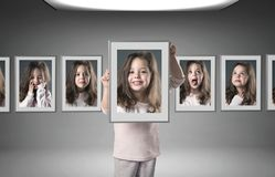 Little girl among lots of her portraits stock photography