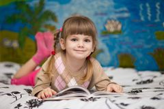 Little cheerful girl read book in bed. Concept of kids knowledge Stock Photography