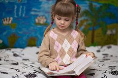 Little cheerful girl read book in bed. Concept of kids knowledge Royalty Free Stock Photo