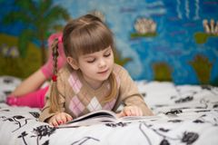 Little cheerful girl read book in bed. Concept of kids knowledge Royalty Free Stock Photos