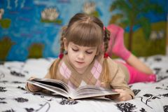 Little cheerful girl read book in bed. Concept of kids knowledge Royalty Free Stock Image