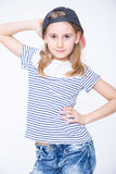 Little cheerful girl schoolgirl with blond hair and cap hat Royalty Free Stock Image
